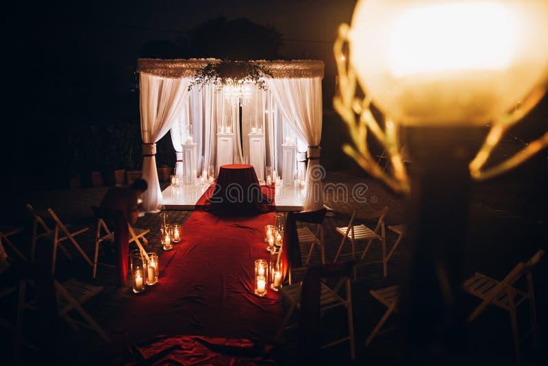 Pasillo del lugar de la boda con las velas en las linternas y el arco de cristal, pocilga imagen de archivo libre de regalías