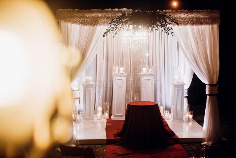 Pasillo del lugar de la boda con las velas en las linternas y el arco de cristal, pocilga imágenes de archivo libres de regalías