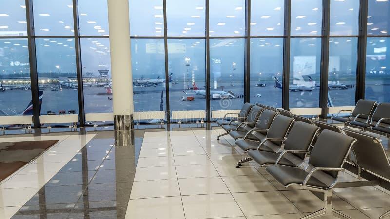 Pasillo del terminal de aeropuerto internacional, vista del campo de aviación a través de la ventana, concepto del viaje foto de archivo