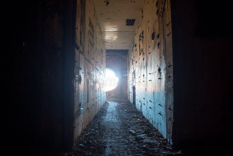 Pasillo espeluznante en central nuclear abandonada con la luz del agujero redondo imágenes de archivo libres de regalías