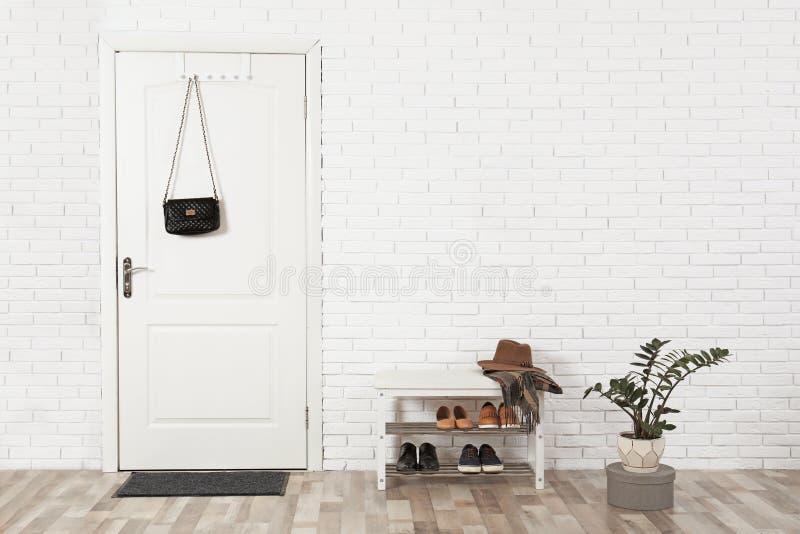 Pasillo interior con la pared de ladrillo y la puerta blanca imagen de archivo libre de regalías