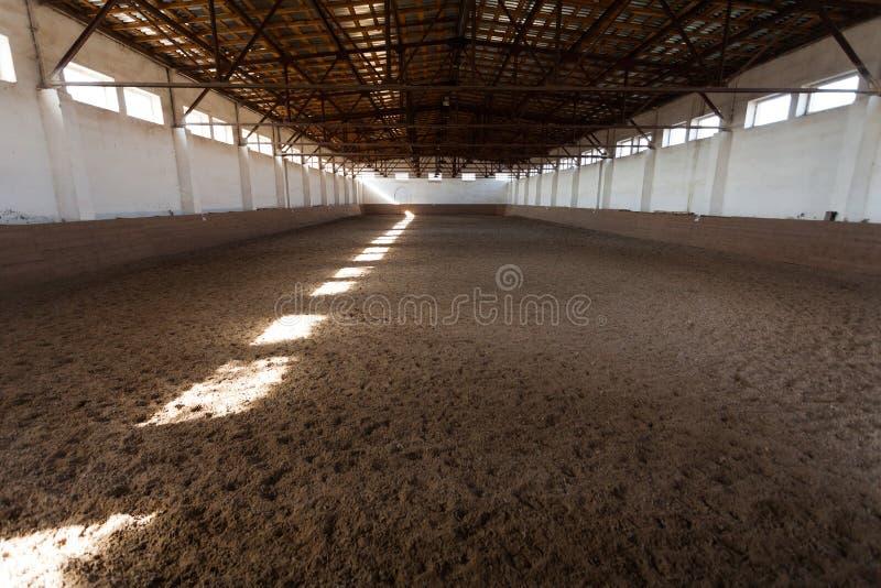 Pasillo interior del montar a caballo con la cubierta arenosa Rayos de la luz a través de las ventanas fotos de archivo libres de regalías