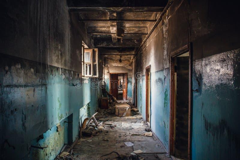 Pasillo oscuro vacío sucio en el edificio abandonado quemado después del fuego, puertas rotas, basura, perspectiva fotos de archivo