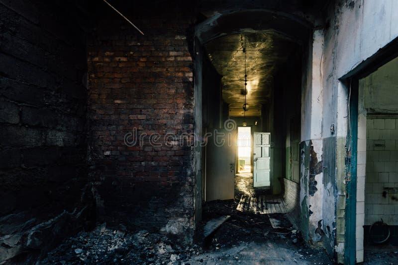 Pasillo siniestro y espeluznante del hospital abandonado después del fuego Techo en hollín negro foto de archivo
