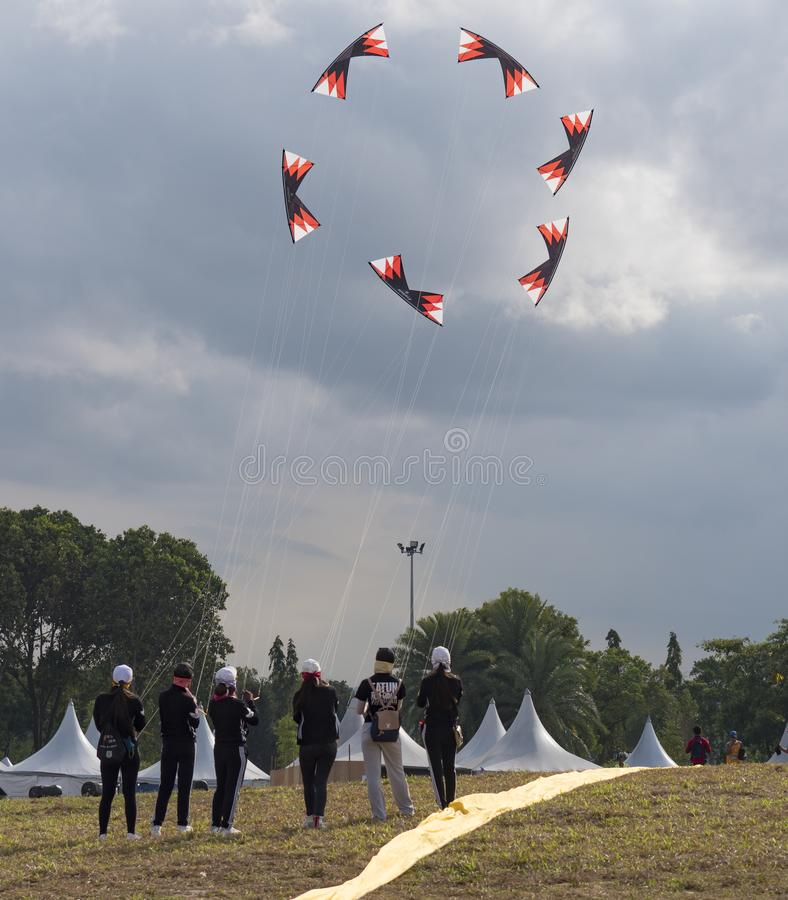 Pasir Gudang World Kite Festival 2018. Pasir Gudang, Malaysia - March 1, 2018: Female, Chinese stunt flying team performing formation flying with 4-line kites at royalty free stock photo