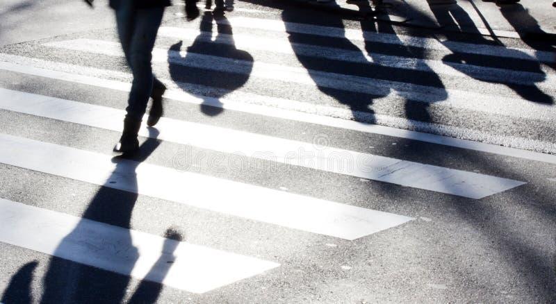 Paso de cebra borroso con los peatones que hacen sombras largas foto de archivo