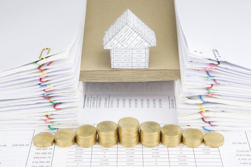 Paso de las monedas de oro con la casa en sobre entre el papeleo foto de archivo