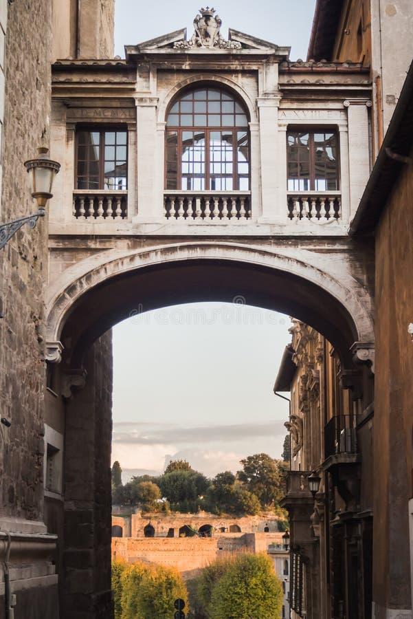 Paso debajo de un puente viejo entre dos edificios en Roma imagen de archivo libre de regalías