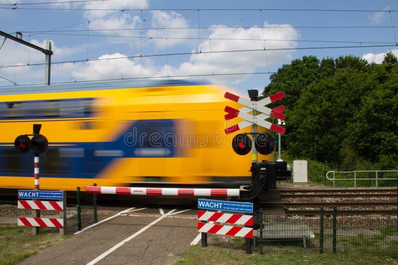 Paso a nivel de la pequeña bicicleta con el tren que pasa cerca en velocidad imagen de archivo libre de regalías