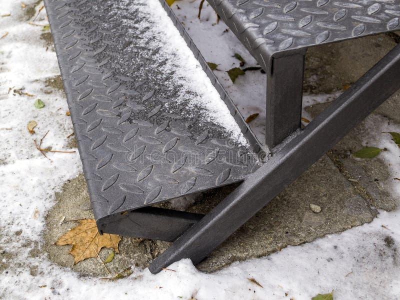 Pasos acanalados de la escalera del hierro pulverizada con la primera nieve foto de archivo