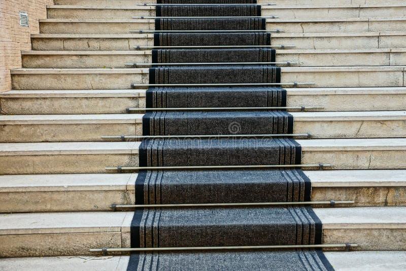 Pasos concretos grises de las escaleras y de la pista negra de la alfombra fotografía de archivo