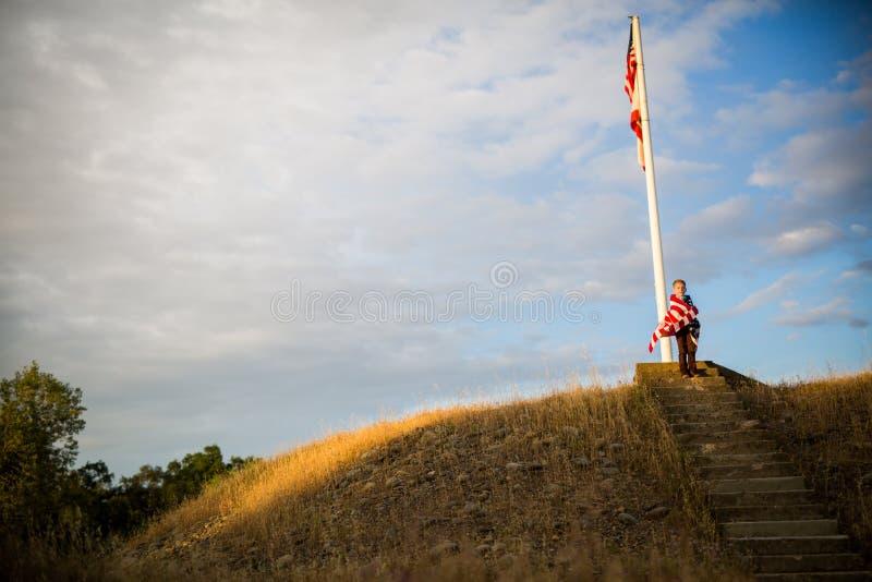 Pasos de progresión a la libertad Un muchacho joven con una bandera americana, alegría de ser un americano imagen de archivo libre de regalías