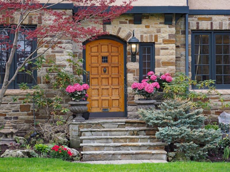 Pasos delanteros de la casa de piedra con la puerta de madera elegante fotos de archivo libres de regalías