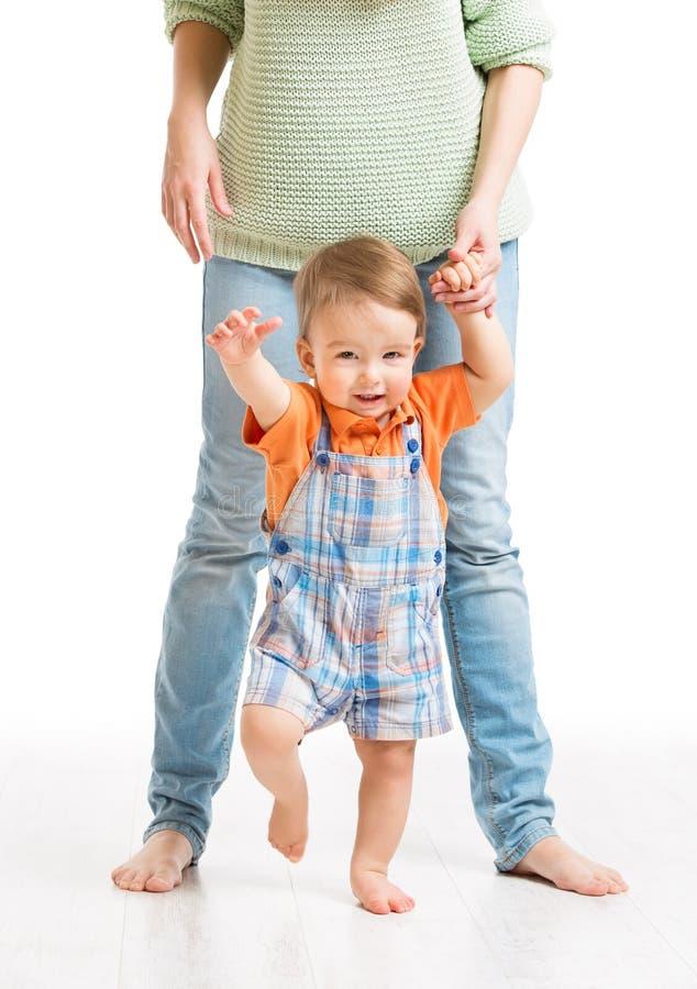 Pasos que caminan del bebé primeros, niño de ayuda de la madre a ir, en blanco foto de archivo