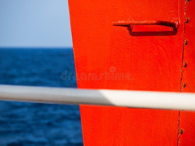 Pasos que cercan con barandilla rojos en una nave - imagen del alto contraste - barra blanca de la manija en el primero plano fotos de archivo libres de regalías