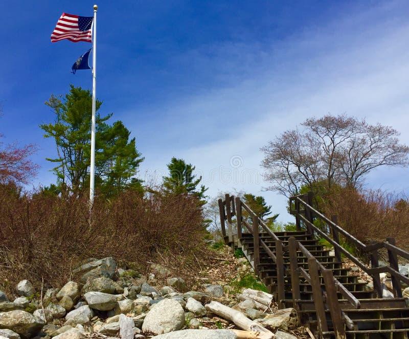 Pasos que llevan de línea de la playa rocosa a la asta de bandera con la bandera de Estados Unidos y de Maine State imagen de archivo libre de regalías