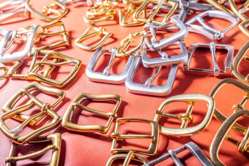 Pasowe klamry na czerwonym pełnym zbożowej skóry tle zdjęcie royalty free