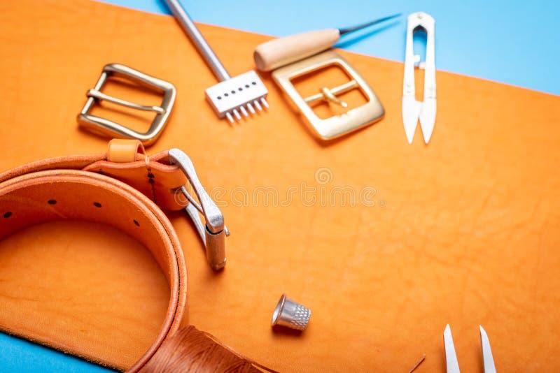 Pasowe klamry z rzemiennymi narzędziami na pomarańczowym pełnym zbożowej skóry tle Materiały, akcesoria na craftman pracy biurku obrazy royalty free