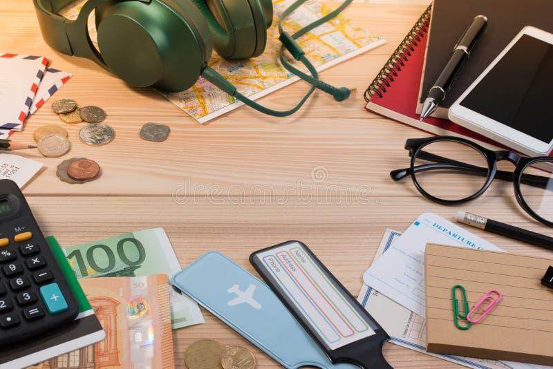 Paspoort, euro muntstuk, euro bankbiljet, hoofdtelefoons, paspoort, toeristische kaart en reizigerslevering op lijst van het bure royalty-vrije stock afbeelding
