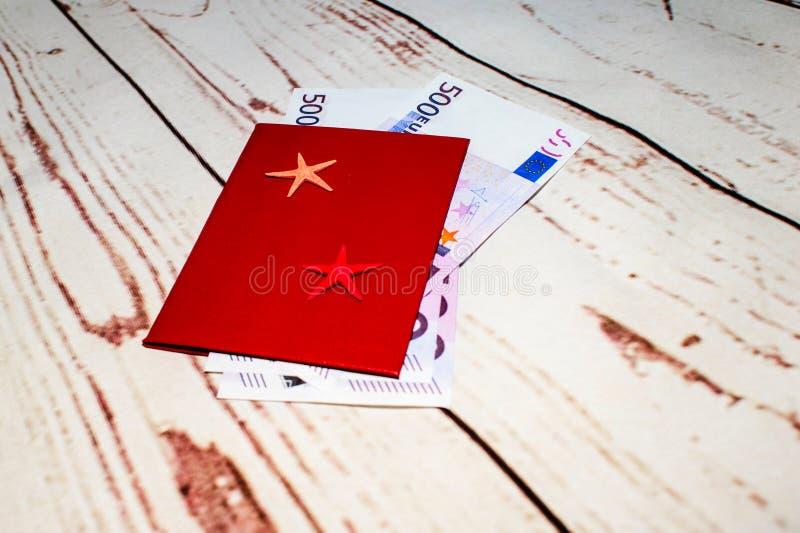 Paspoort met geldrekeningen en shell in bijlage Het concept reis royalty-vrije stock afbeeldingen