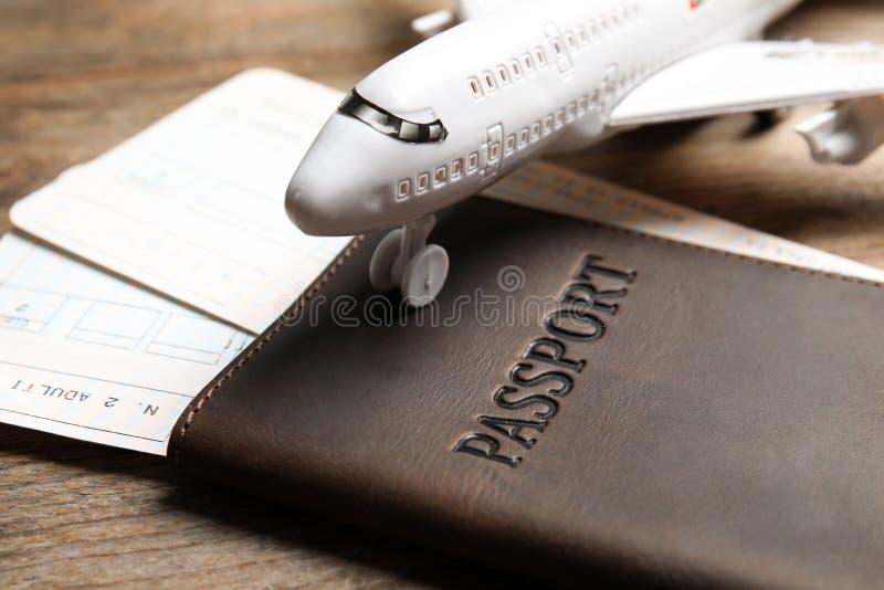 Paspoort met kaartjes en stuk speelgoed vliegtuig op houten lijst, close-up royalty-vrije stock afbeeldingen