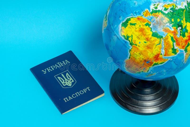 Paspoort van een burger van de Oekra?ne dichtbij de bol op een blauwe achtergrond stock fotografie