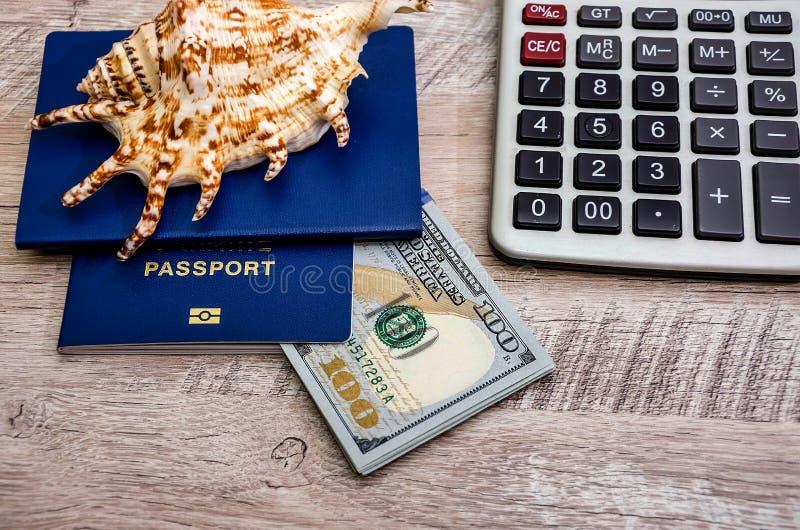 Paspoorten, dollars, calculator op een houten achtergrond stock foto