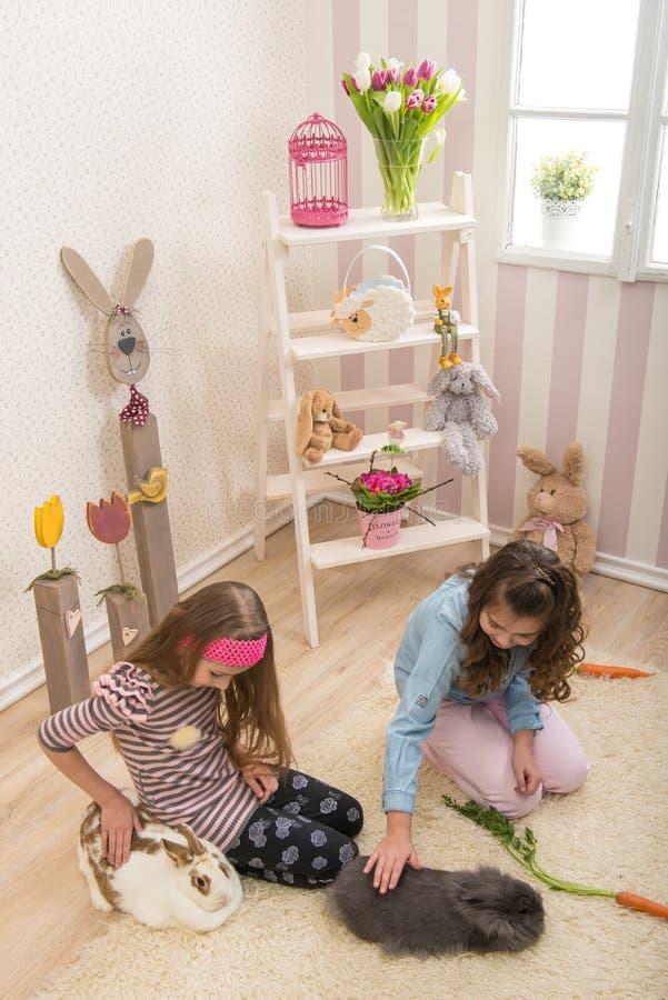 Pasqua - bambine che segnano i conigli, barbabietole della mano immagini stock