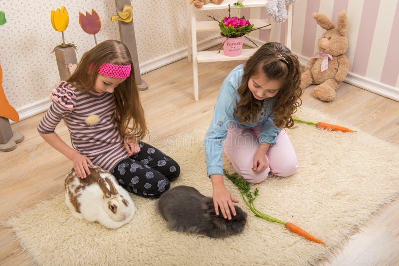 Pasqua - bambine che segnano i conigli, barbabietole della mano fotografie stock libere da diritti