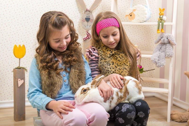 Pasqua - bambine che segnano il coniglietto enorme e in tensione fotografia stock