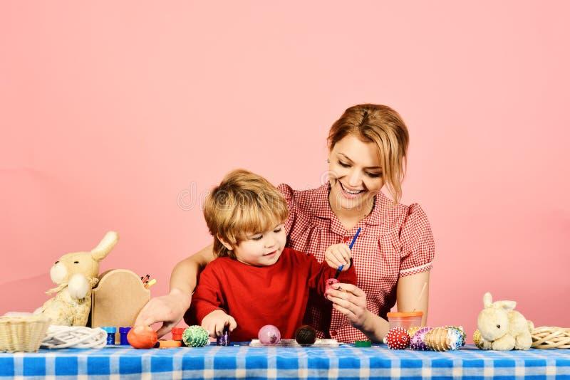Pasqua e concetto felice di momenti Uova della pittura del figlio e della madre immagini stock libere da diritti