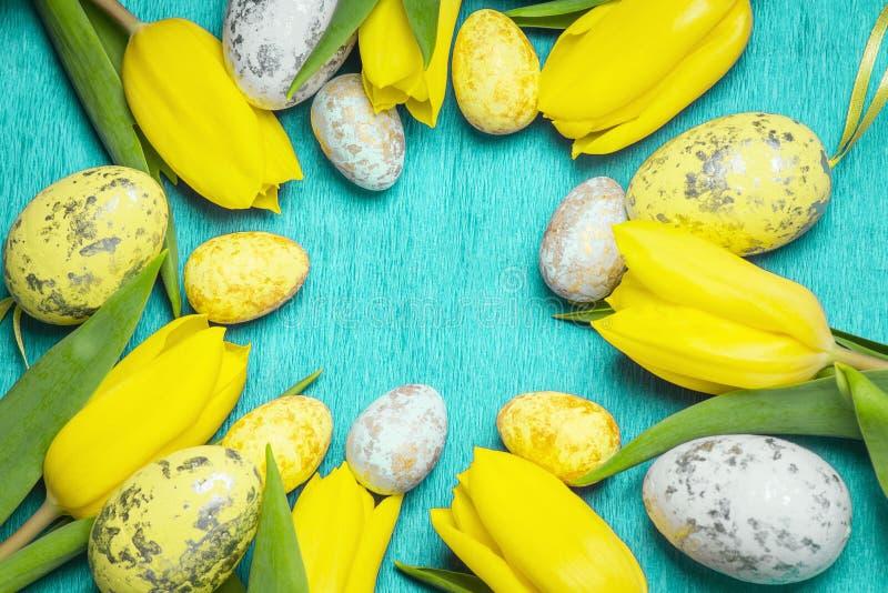 Pasqua felice I tulipani freschi gialli si trovano su un fondo blu con le uova di Pasqua immagine stock