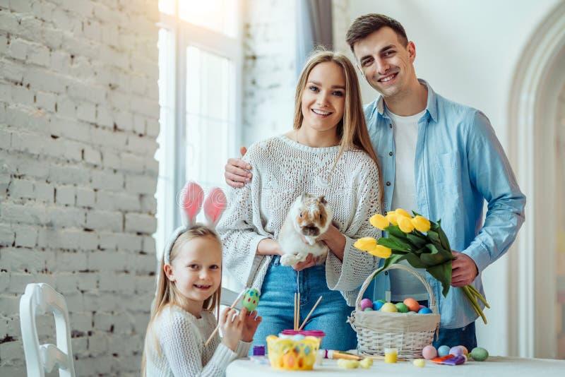 Pasqua felice! Il papà tiene un mazzo dei tulipani, la mamma tiene un coniglio decorativo domestico, la figlia dipinge le uova e  immagini stock