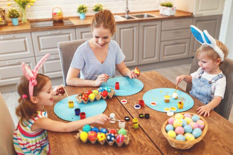 Pasqua felice! la madre ed i bambini della famiglia dipingono le uova per il holida immagine stock