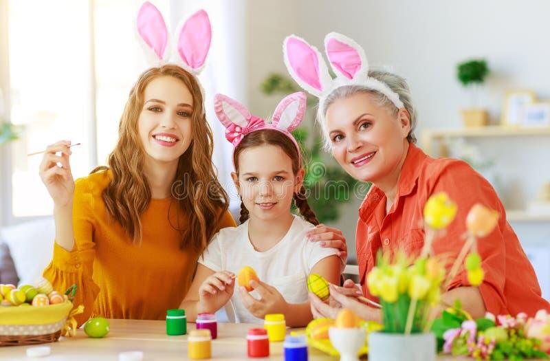 Pasqua felice! la nonna, la madre ed il bambino della famiglia dipingono le uova e preparano per la festa fotografie stock libere da diritti