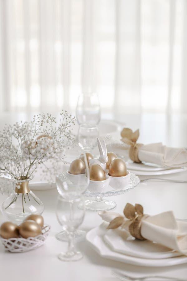 Pasqua felice! Regolazione dorata della tavola e della decorazione della tavola di Pasqua con i piatti bianchi di colore bianco fotografia stock libera da diritti