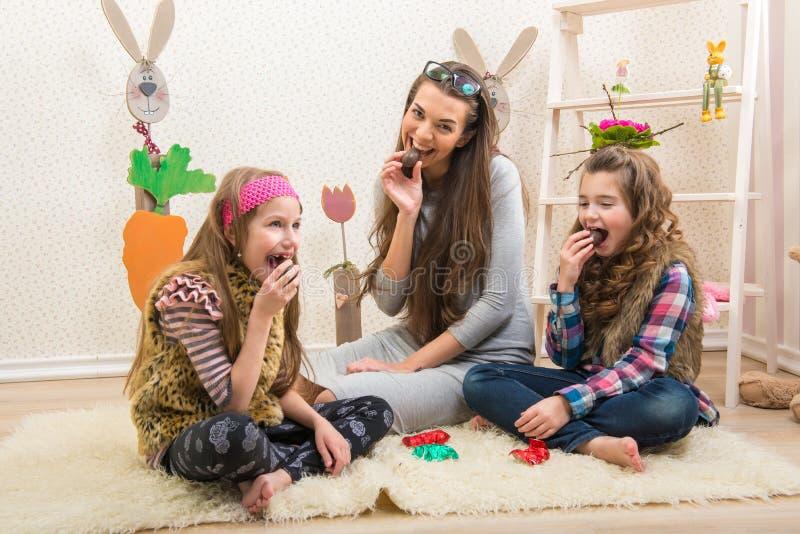 Pasqua - la madre e due figlie mangiano le uova di cioccolato fotografia stock