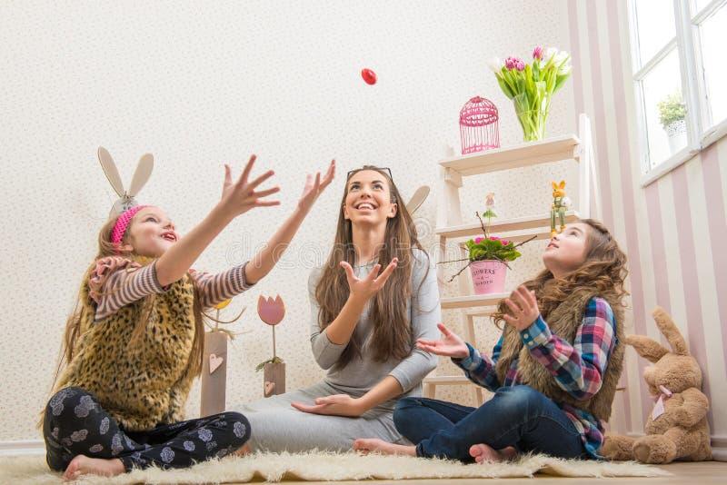 Pasqua - madre e due uova di cioccolato delle figlie gettate fotografie stock