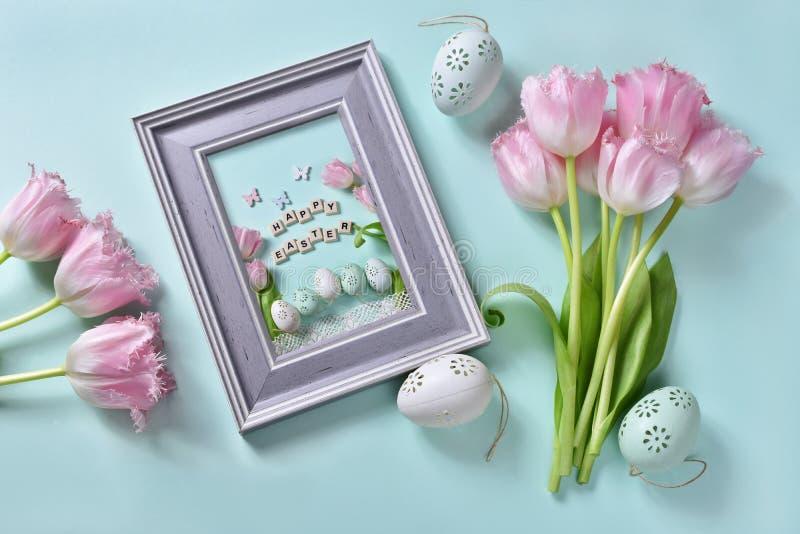 Pasqua pone pianamente con il mazzo di tulipani e di cartolina d'auguri rosa nel telaio immagini stock libere da diritti