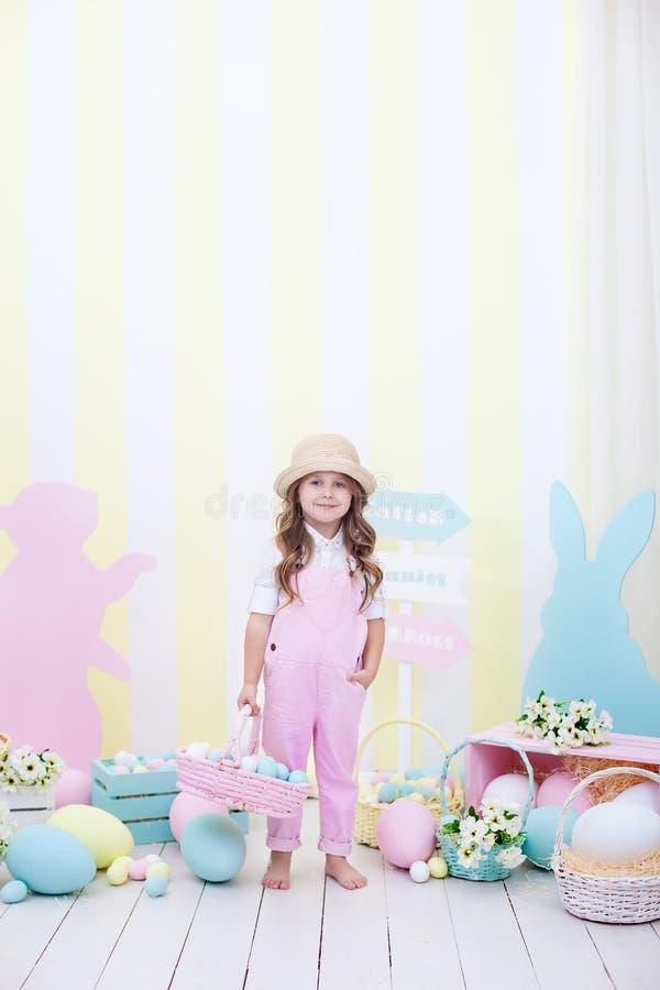 Pasqua! Una ragazza sveglia è stante e tenente un canestro con le uova in sue mani con una decorazione nei precedenti La ragazza  fotografie stock