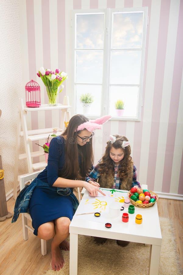 Pasqua - uova della pittura della figlia e della madre, orecchie del coniglietto su loro fotografia stock