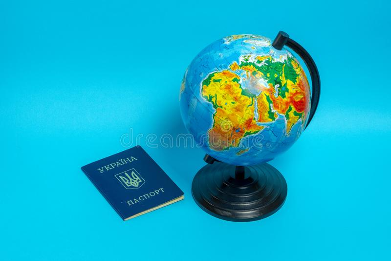 Pass av en medborgare av Ukraina n?ra jordklotet p? en bl? bakgrund royaltyfria foton