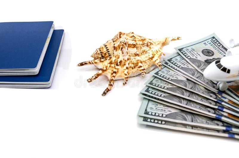 Pass, dollar och snäckskal på en vit bakgrund royaltyfri fotografi