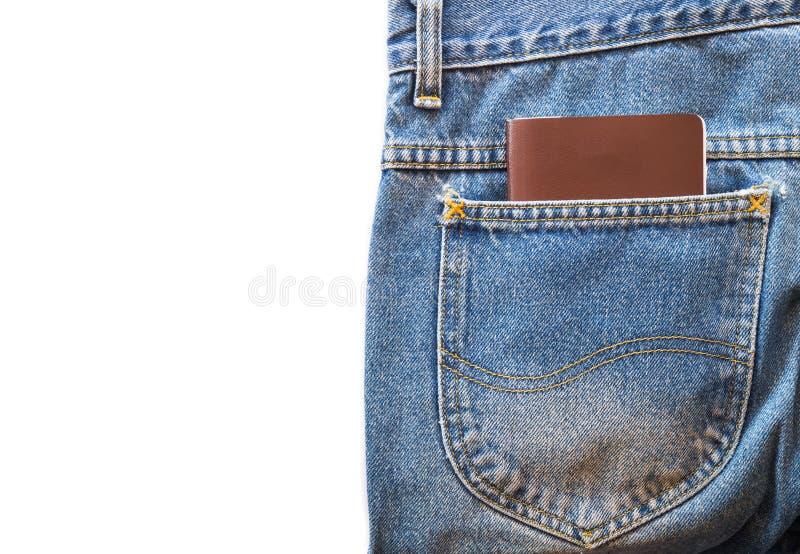 Pass- eller mellanrumsanmärkningsboken i jeans stoppa i fickan på vit isolerad bakgrund royaltyfria bilder