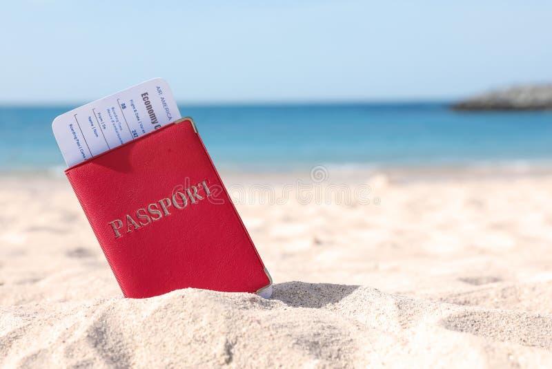 Pass med flygbolagbiljetten i sand på stranden arkivbilder