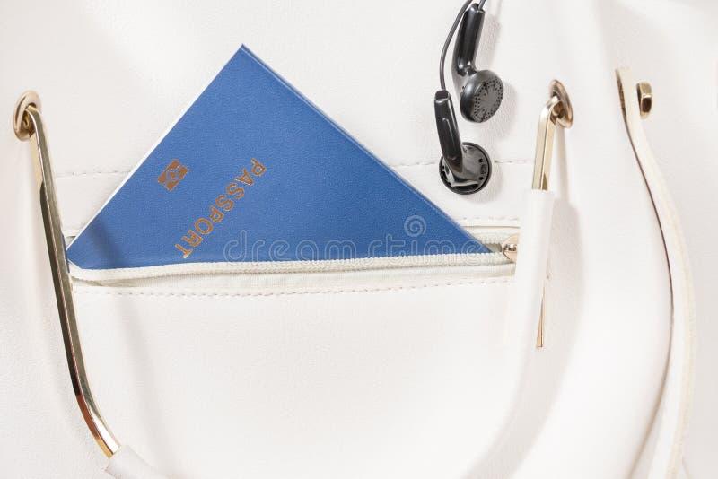 Pass och hörlurar i handväska royaltyfri foto