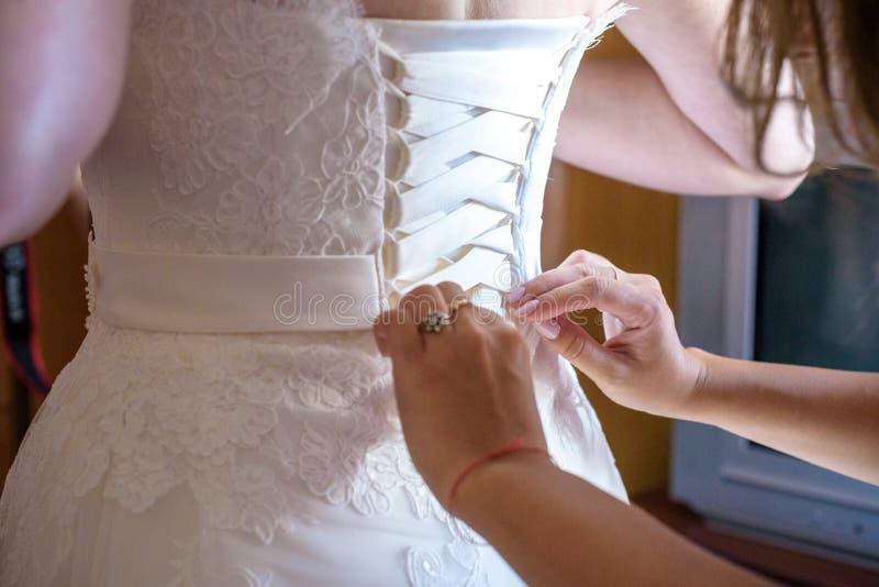 Passa il primo piano che allaccia il corsetto del vestito da sposa immagini stock libere da diritti