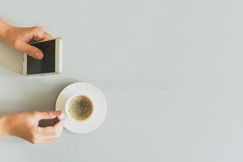 Passa la donna che per mezzo dello Smart Phone sulla tavola di legno grigia Tempo del caffè Rituale di mattina fotografie stock libere da diritti