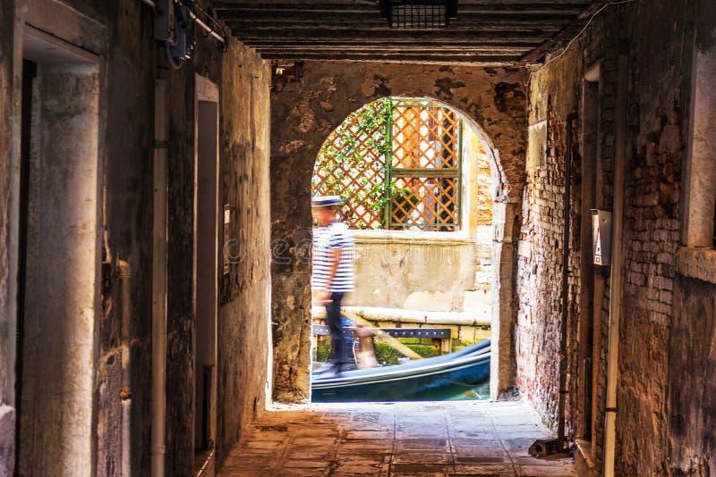 Passage à Venise et une silhouette d'un gondolier dans un canal photographie stock libre de droits