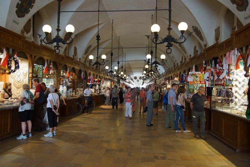 Passage avec des stalles de souvenir du hall gothique Sukiennice, place principale du marché, Cracovie image libre de droits